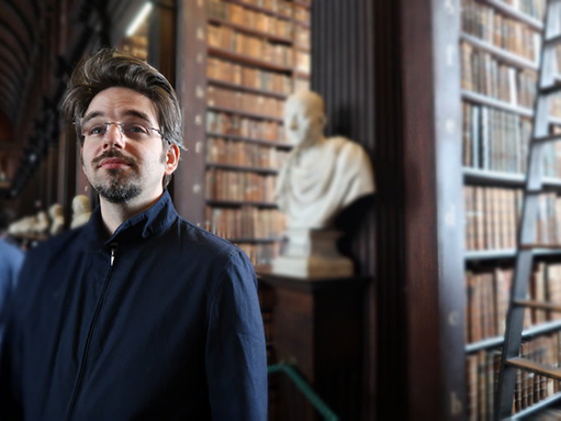 Daniel Pettersson with bookshelves and a marble bust of Cicero in the background, at the Trinity College Library, Dublin.