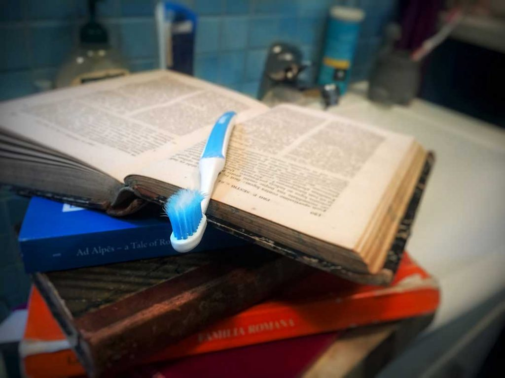 Latin daily habit illustrated by a toothbrush laying on top of a pile of Latin books, the top one open.