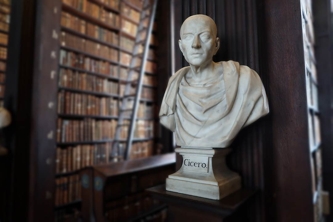 White marble bust of Cicero with the Trinity College Library, Dublin, in the background.