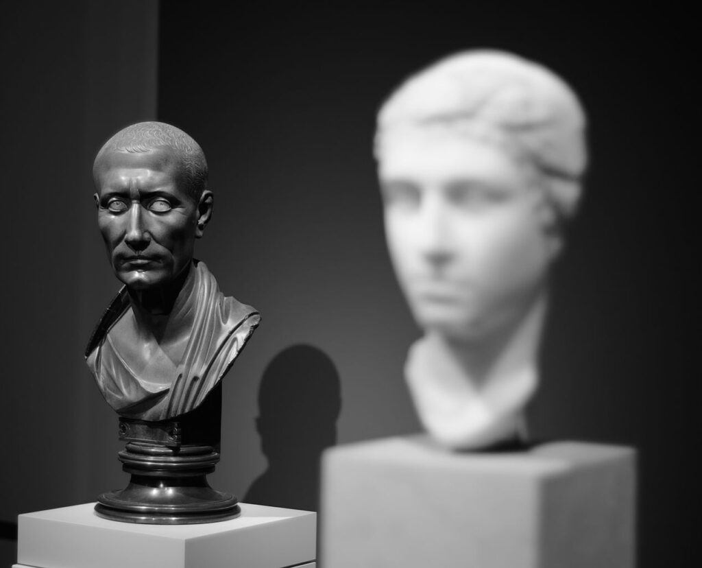 A black marble bust of Julius Caesar seemingly looking at a white warble bust of Cleopatra.