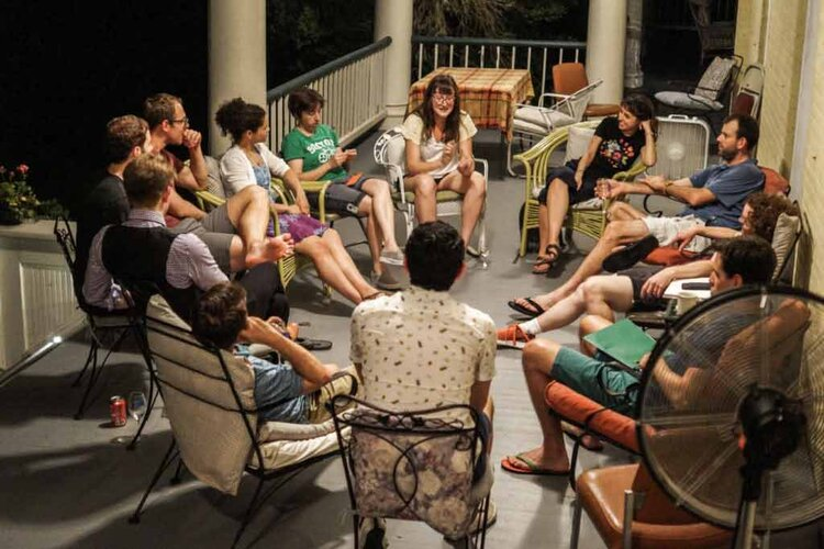 Group of Latin student in talking in a circle on a porch.