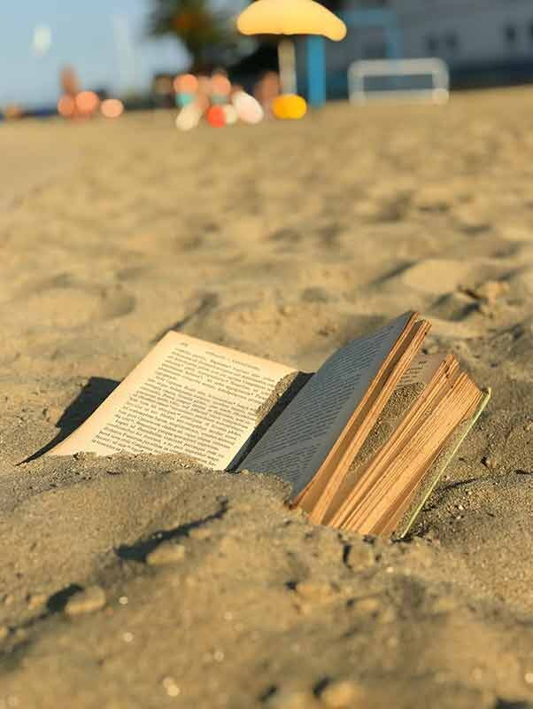 An open Latin book filled with sand on a beach.