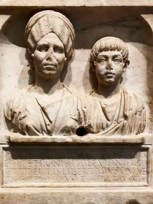 Funerary inscription in stone from early 2nd century with busts of a Roman woman and a young boy.
