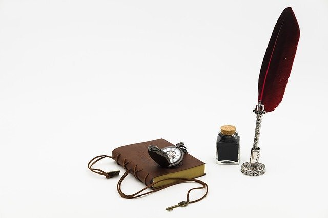 A red feathered pen with ink and a leather bound notebook.
