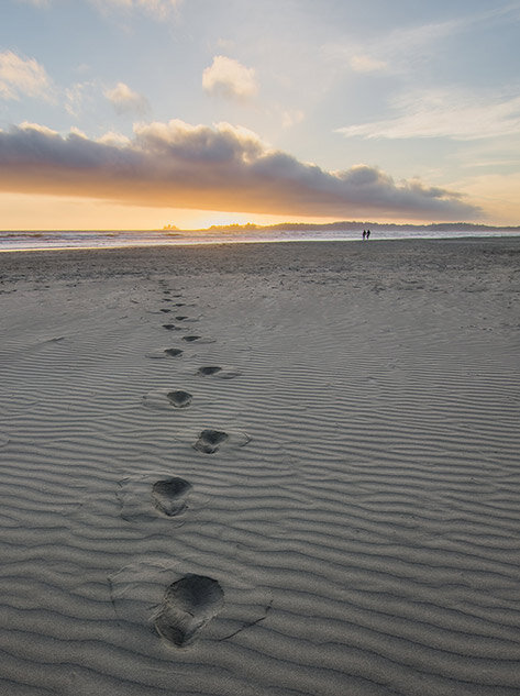 Footsteps on a beach towards the sea and the setting sun to illustrate distance.