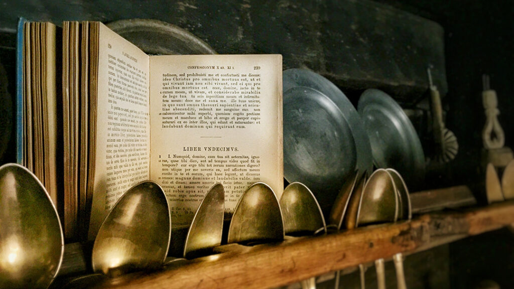 Augustinus' Confessiones open in the middle, standing amongst spoons and old plates in a kitchen.