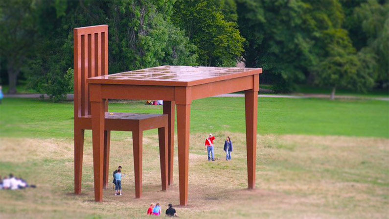 A sculpture of a giant table and chair, by Giancarlo Neri.
